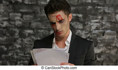 Vampire reads and tears paper in anger - Male vampire reads...