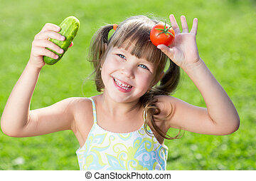 Happy little girl over the grass with a  vegetables at summer time. Concept of healthy food.