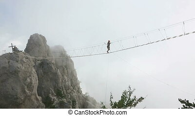 Woman over precipice - Woman walking on the rope bridge over...