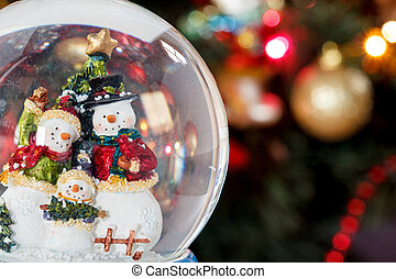 Snow globe with happy snowman family on christmas tree...