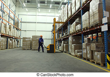 work in warehouse - worker in blue uniform in the warehouse