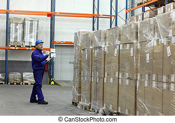 counting stocks - worker in blue uniform counting stocks in...