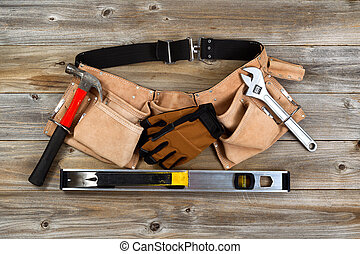 Leather tool belt with tools on rustic wooden boards -...