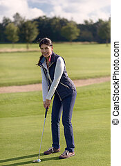 Female golfer putting on green
