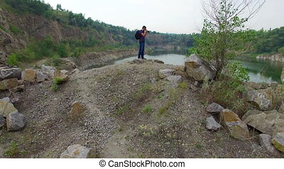 Aerial: Man takes photos on rock - Aerial: Man takes photos...