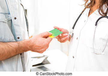 Young attractive doctor taking health insurance card - View...
