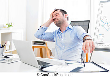 Young attractive man too tired to work - View of a Young...