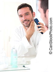 Young attractive man shaving his beard in front of a mirror...