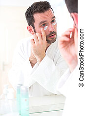 Young attractive man applying anti dark circles cream around...