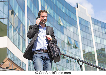 Young attractive business man using smartphone - View of a...