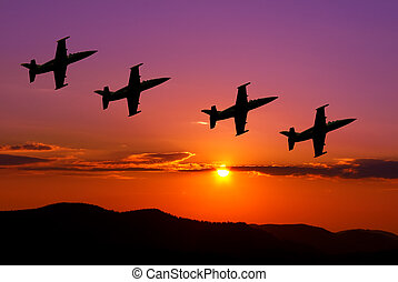 Fighter jets in the sky at sunset
