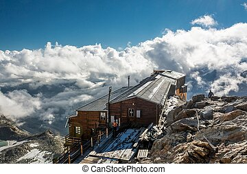 Mountain cabin. Mountain view with a cabin and clouds...
