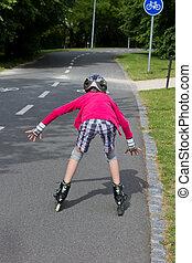 Little girl rolller skating in a park - Girl roller skating...