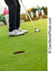 Golf player at the putting green. Hitting ball into a hole