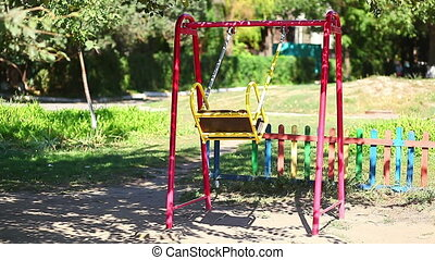 Empty children's swing in summer park