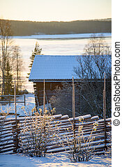 Rural winter scene. Old fence in front. Wodden brarn, a few...