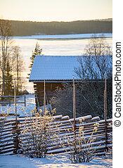 Rural winter scene. Old fence in front. Wodden brarn, a few...