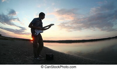 street musician takes his guitar and starts playing at...