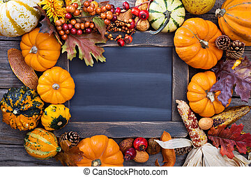 Pumpkins and variety of squash aroun a chalkboard