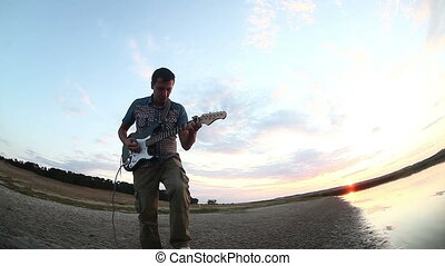street musician begins to play electric guitar at sunset the...