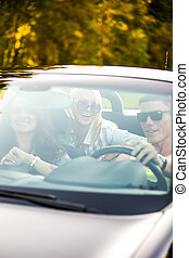 Friends driving car - Group of three carefree cheerful...