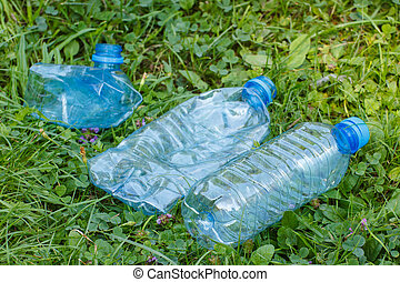 Plastic bottles of mineral water on grass in park, littering...