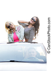 Friends going on holidays in car - Group of three carefree...