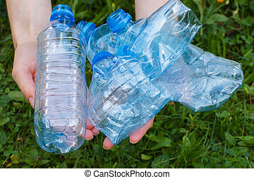 Plastic bottles of mineral water in hand of woman, littering...