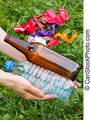 Plastic and glass bottle in hand of woman, littering of...