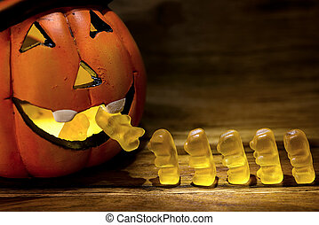 trick or treat - halloween pumpkin eating a row of gummy...
