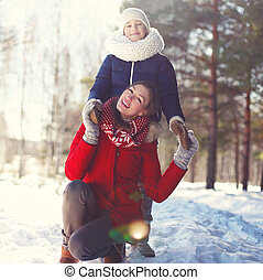 Portrait of smiling mother with son in winter park