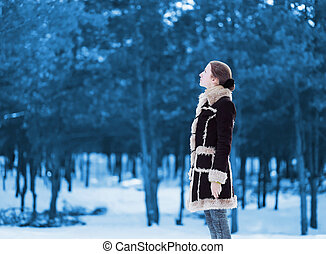 Silhouette woman standing  profile and looks up wearing a brown coat in winter snowy forest