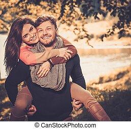 Cheerful couple in autumn park having fun