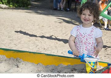 In the summer at the playground little girl playing in the sandbox.