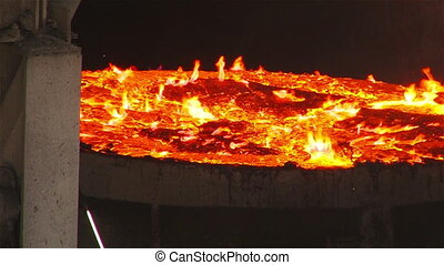 Burning metal vat - Molten metal melted in furnace at...
