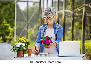 Working in a flower shop - Beautiful mature woman working in...