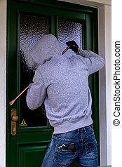 burglar at a house door - a burglar trying to break a door.