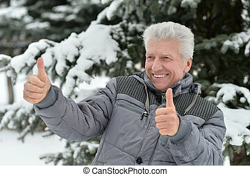 Elderly man in winter with thumbs up