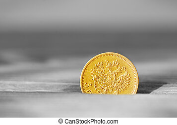 Ancient golden coin on a wooden table