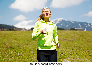 happy young smiling woman jogging outdoors - fitness, sport,...