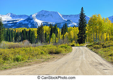 road through the alpine scenery of yellow and green aspen...
