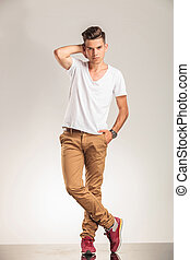 young man standing with legs crossed on beige studio...