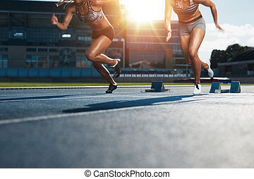 Sprinters starts out of the blocks on athletics racetrack...
