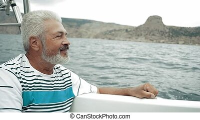 Senior Man Sitting On Boat Looking