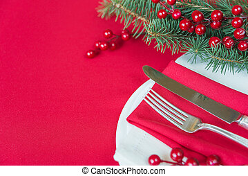 Christmas table - Silver knife and fork lie on the red linen...