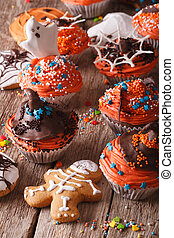 festive Halloween cupcakes and gingerbread cookies closeup. vertical