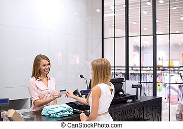 Consumerism - Woman at the checkout makes shopping