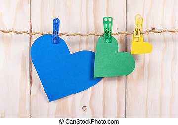 Color hearts hanging on rope on wooden background