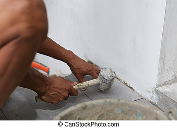 Man laying tile with rubber hammer - Man laying floor tile...