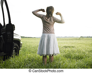 Woman in Field Stretching - Rear view of woman outside of...